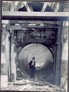 A man dressed in his Sunday best posing inside a penstock